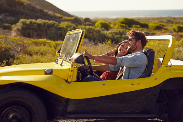 Young man with his girlfriend on road trip in a open top car