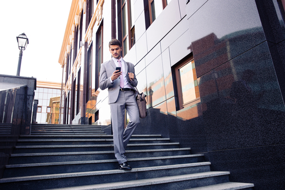 Businessman walking on the stairs and using smartphone outdoors - How To Draw In An Aquarius Man Via Text