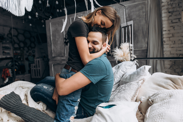 Loving couple hug each other on the bed - How Does An Aquarius Man Fall In Love
