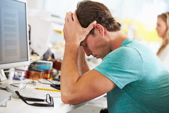 Stressed Man Working At Desk In Busy Creative Office - Why would an Aquarius Man ignore you