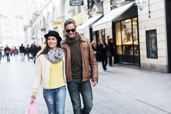 The woman is wearing a black hat and a pink shopping bag and the man has sunglasses and a leather coat - Are Aquarius Men Possessive Of Their Partner
