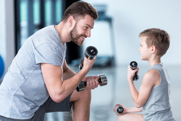 Father and son working out at the gym